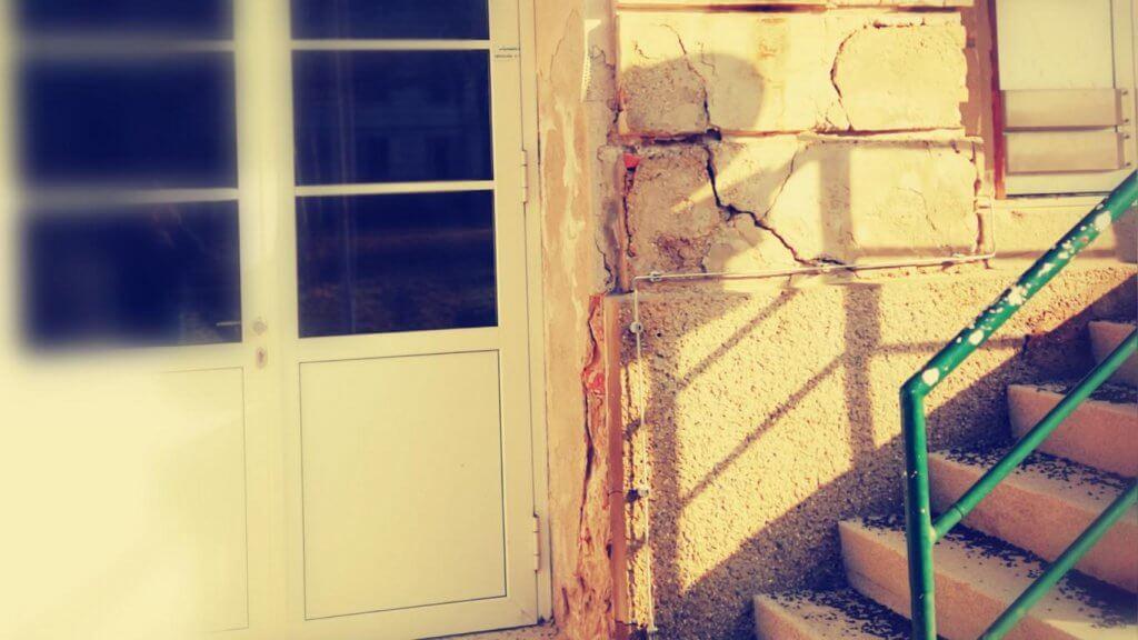 Durch Feuchtigkeit im Mauerwerk bröckelt der Fassadenputz an einer Hausecke ab.