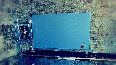 Ein INTROC Lautlostrockner trocknet feuchtes Mauerwerk im Keller und steht mit wenigen Zentimetern Abstand vor der Mauer.