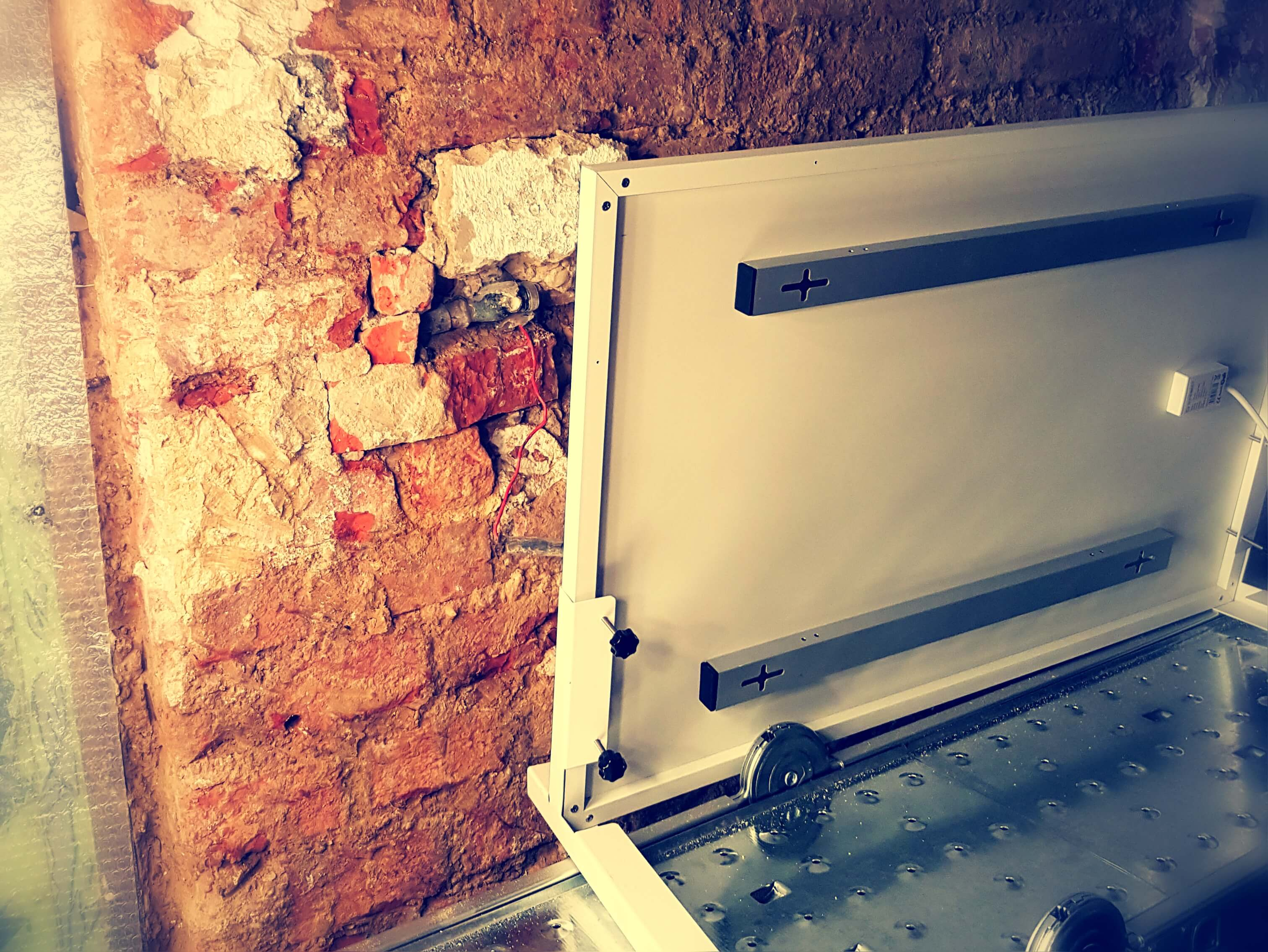 Ein Bautrockner ist auf einem Gerüst aufgestellt und trocknet das sanierungsbedürftige Mauerwerk.