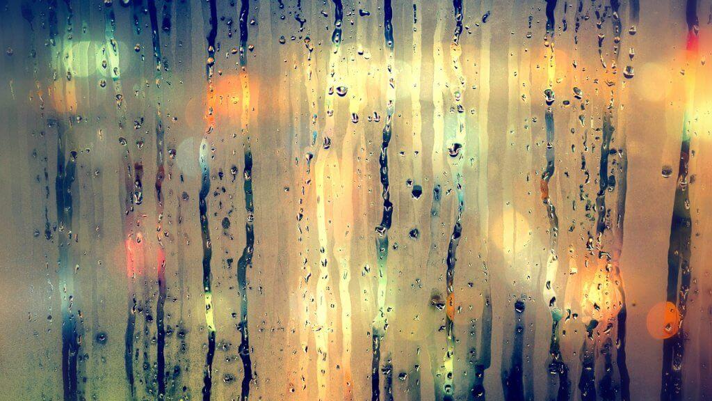 Die Luftfeuchtigkeit sammelt sich auf einer Fensterscheibe. Im Hintergrund sind die Lichter einer Stadt zu sehen.